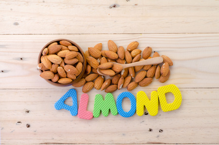 Almonds in brown bowl on wooden background.