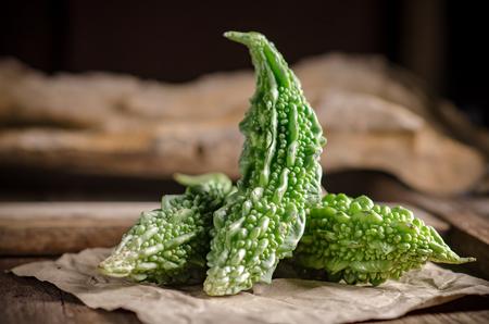 Rohe grüne organische bittere Melone auf Holztisch