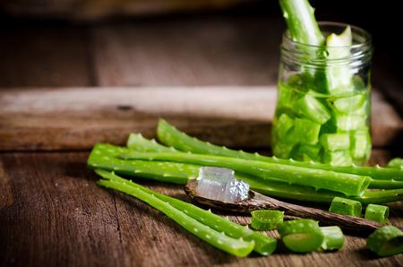 aloe vera gel on wooden spoon with aloe vera on wooden table.