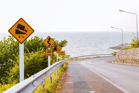 dangerous road: Road signs on dangerous road near the sea Stock Photo