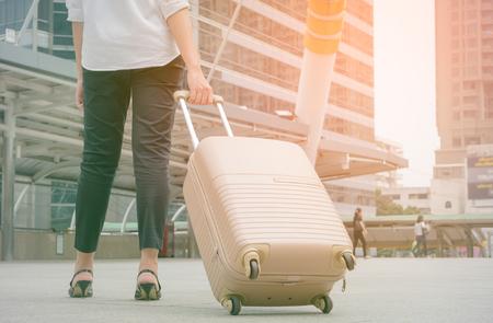 Donna che tira la valigia in città moderna, stile vintage tono