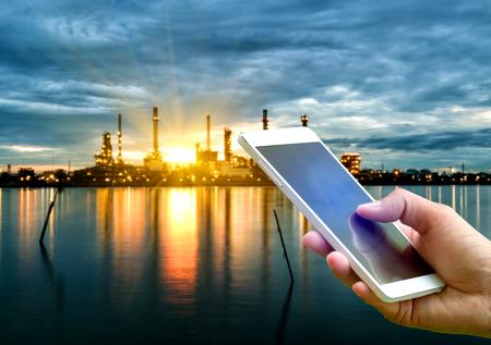 Mano que sostiene teléfono inteligente en la planta de la industria de refinería de petróleo borrosa a lo largo de la mañana el crepúsculo