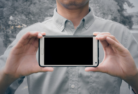 snapping fingers: Man holding mobile smart phone black LCD  with clipping path for the screen (vintage style color) Stock Photo