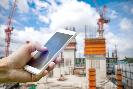 Hand holding smartphone on blurred construction site workers with cloud and blue sky 스톡 콘텐츠