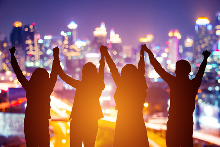 Silhouette of happy business team making high hands in blurred cityscape background for business teamwork concept