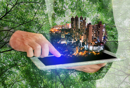 Double Exposure man touch screen taplet with tree background and cityscape,civilize concept