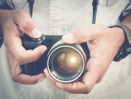Photographer holding mirorless camera with sunflare 스톡 콘텐츠