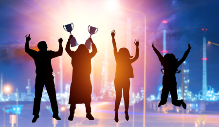 Silhouette four business people make high hands and jumping when business success and trophy receive.
