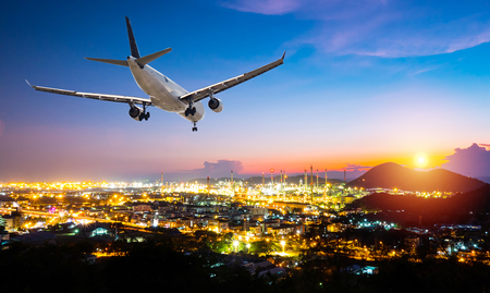 Airplane for transportation flying over the night scene city on sunset background. Travel transportation concept. Stock Photo