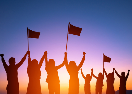 Silhouette of happy business team making high hands and holding flags in sunset background for business teamwork concept.Business succes concept. Stock Photo
