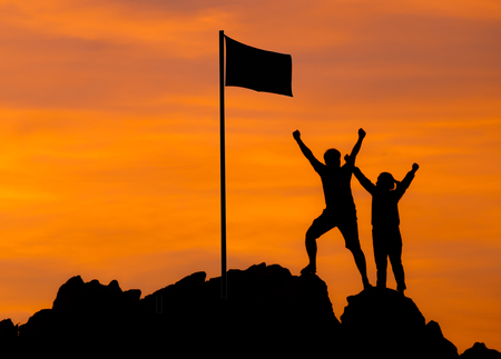 High success, Two people silhouette make high hand with flag of victory on top of mountain, hands up Conceptual teamwork,business teamwork. Against the dramatic sky at sunset.