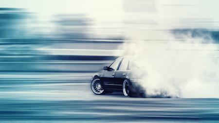 Auto alla deriva, auto da corsa offuscata di diffusione dell'immagine con un sacco di fumo dalle gomme in fiamme sulla pista di velocità