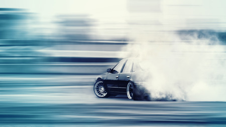 Car drifting, Blurred of image diffusion race drift car with lots of smoke from burning tires on speed track Stock Photo