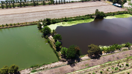 Aerial view from flying drone of wastewater treatment ponds and ponds for plant. It is divided by clay a dirt to prevent pollution from sewage flowing from the large dump.Pollution from toxic waste dumps concept.