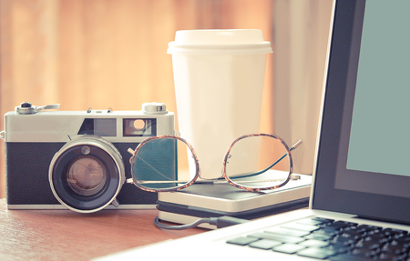 Film camera,cup of coffe,eye glasses,hard drive with laptop on wood desk.