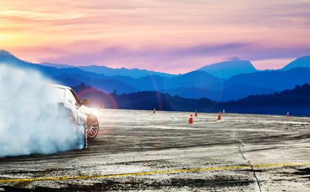 Auto drammatica alla deriva, auto da corsa offuscata di diffusione dell'immagine con un sacco di fumo da pneumatici in fiamme sulla pista di velocità Archivio Fotografico
