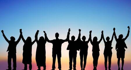 シルエットサンセット背景でのチームワークコラボレーションと自由の成功。ビジネスコンセプトを提供します。
