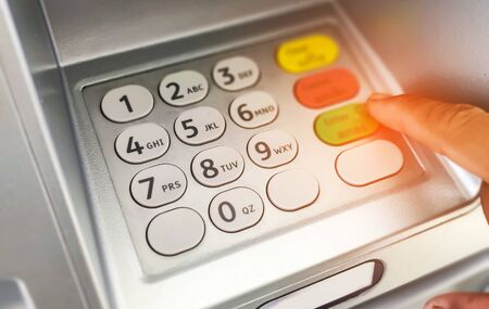 Close-up of hand entering on ATMbank machine keypad. Stock fotó