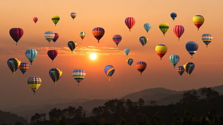 Ballon à air chaud au-dessus de la haute montagne au coucher du soleil