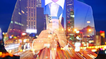 Double exposure image of businessman in suit Remove the necktie with the traffic image in the city at night.