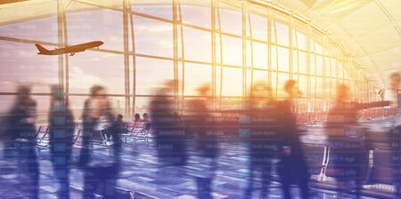Airport terminal at sunset with passengers.
