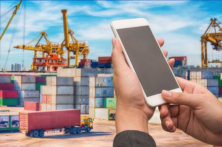 Businesswoman holding smartphone with blurred cargo ship's marine background