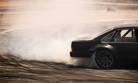 Car drifting, diffusion race drift car with lots of smoke from burning tires on speed track