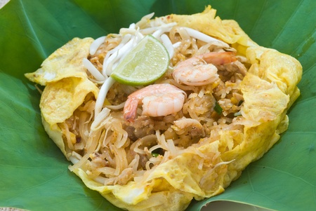 Shrimp Pad Thai wrapped with fried egg on lotus leaf photo