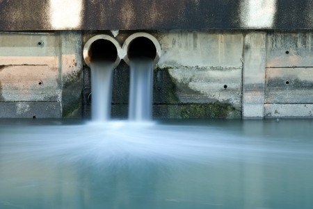 riool: Dirty afvoer vervuilende een rivier Stockfoto