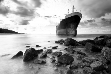Cargo ship run aground on rocky  shore waiting for rescue photo