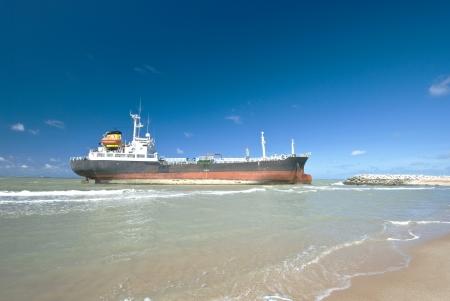 Frachtschiff festfahren felsigen Ufer des Wartens auf Rettung