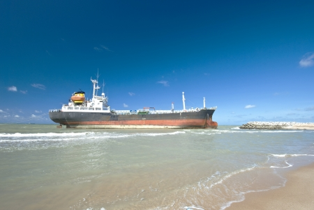 Vrachtschip aan de grond run op de rotsachtige kust wachten op redding