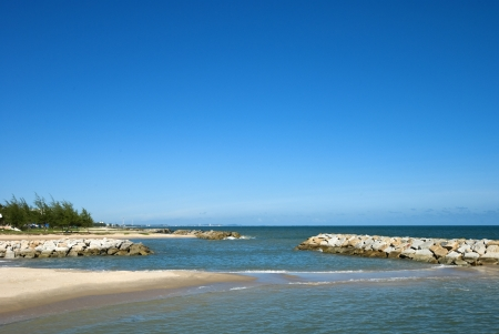 peaceful white sand beach with rocky surf protection in Thailand photo