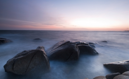 Long exposure of rocky shore over sunset in Thailand photo