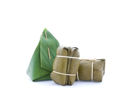 Thai dessert, steam sticky rice with custard cream wrapped with banana leaf isolated photo