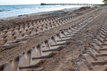 Imprint of tire track on sand beach  photo