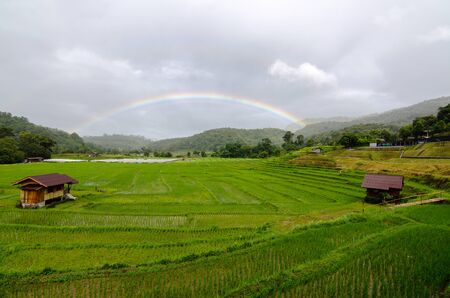 Amazing views of rainbow over rice paddy field in Mae Klang Luang Karen village in Chiangmai, Thailand Stock Photo - 131185184