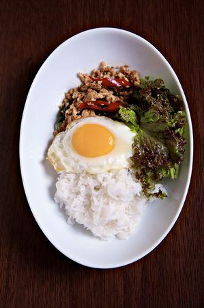 santa cena: Campo de estilo tailand�s fried Chicken picante con Tailandia Basilio Santa encabezando con huevo frito sobre el arroz de jusmine