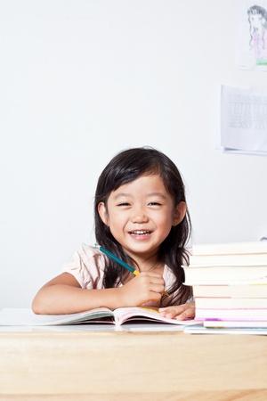 deberes: Retrato de alegre muchacha asi�tica joven que hace su tarea