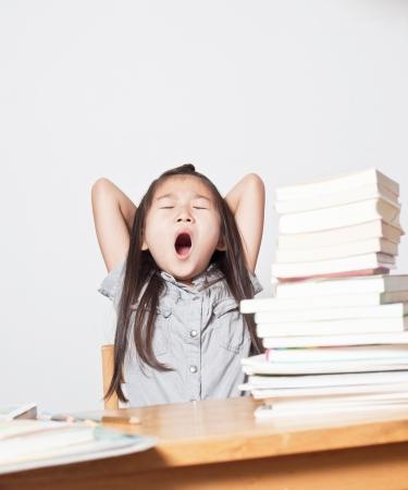 Niña de Asia bostezando en sus libros