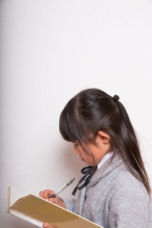 A young school girl thinking and writing photo
