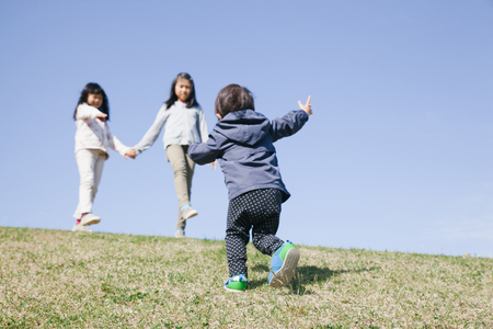 three kids playing on green hill