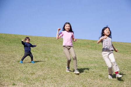 three kids running down from green hill