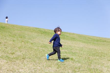 feild: a boy playing on green hill