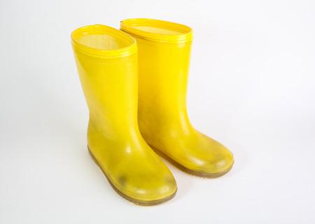 rain boots: botas de lluvia de goma amarillo sobre fondo blanco Foto de archivo