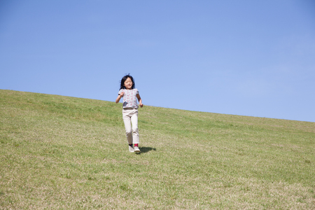 a japanese girl running down from green hill