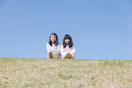 Two Japanese girls sitting on hill