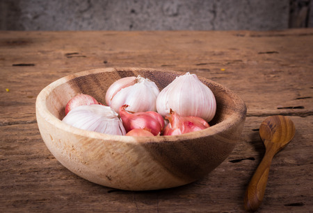 red onions: Garlic and red onions in a wooden bowl.