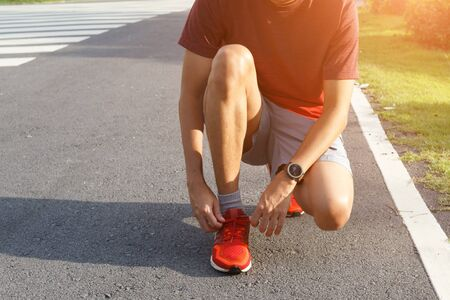 Close-up of sportsman in the tunning park He tying sneakers on running shoes before practice. Running concept.