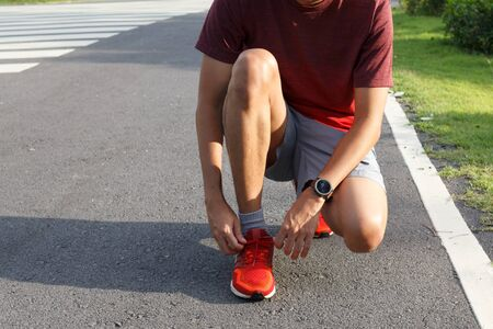 Close-up of sportsman.He tying sneakers on running shoes before practice. outdoor  Running concept.